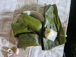 Selbstgemachte Süßigkeit: Reis mit Bananen in Palmenblättern